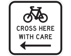 Bicycles cross left sign - class 1 retroreflective Australian standard aluminium or metal guide sign. Features white curved-edge rectangle background